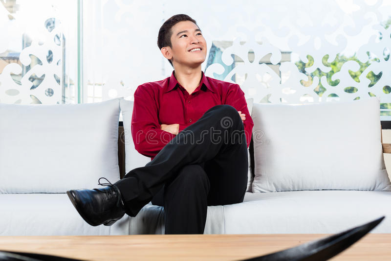 亚裔人坐在家具店的沙发 免版税库存图片