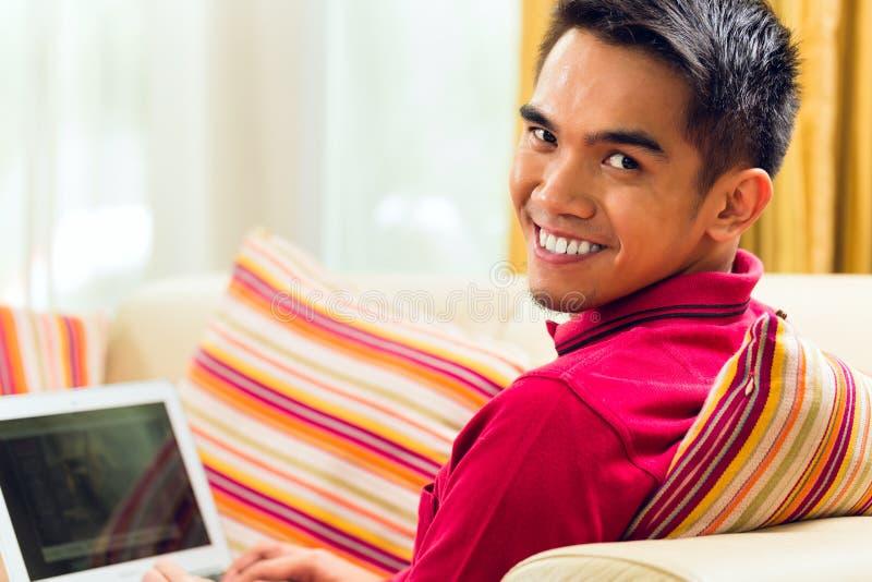 亚裔人坐浏览互联网的长沙发 库存照片