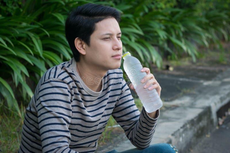亚裔人坐的和饮用水 库存图片