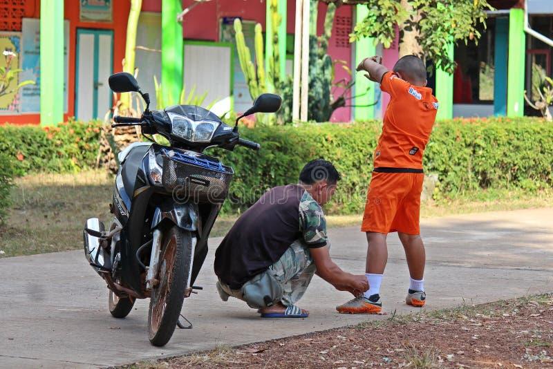 亚裔人束缚儿子的鞋子 库存图片