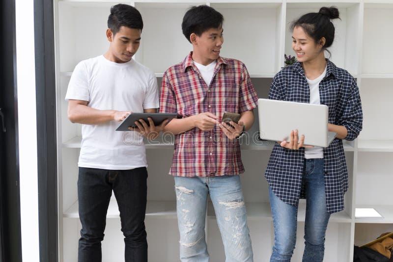 年轻亚裔人民使用不同的小配件和微笑, stan 库存照片