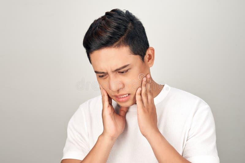 亚裔人画象有忧虑眼睛的使用接触他的面颊,感觉的手从牙痛痛苦 牙和嘴疾病概念 免版税库存图片