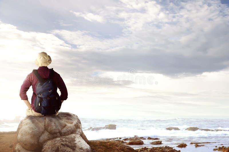 亚裔人背面图帽子的有坐岩石和看海景的背包的 库存照片