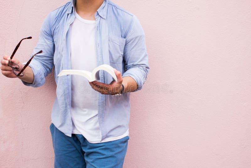 亚裔人英俊在拿着黑玻璃的蓝色衬衣 在桃红色背景的人身分 库存照片