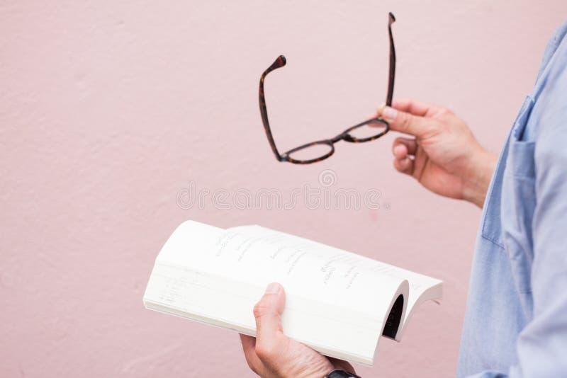亚裔人英俊在拿着黑玻璃的蓝色衬衣 在桃红色背景oudside看书和放松的人身分 免版税库存照片