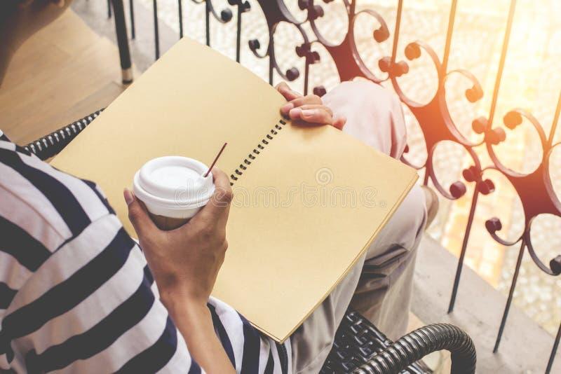 亚裔人英俊有胡子在蓝色衬衣和戴着眼镜黑色 坐在咖啡馆看书和放松的人 库存图片