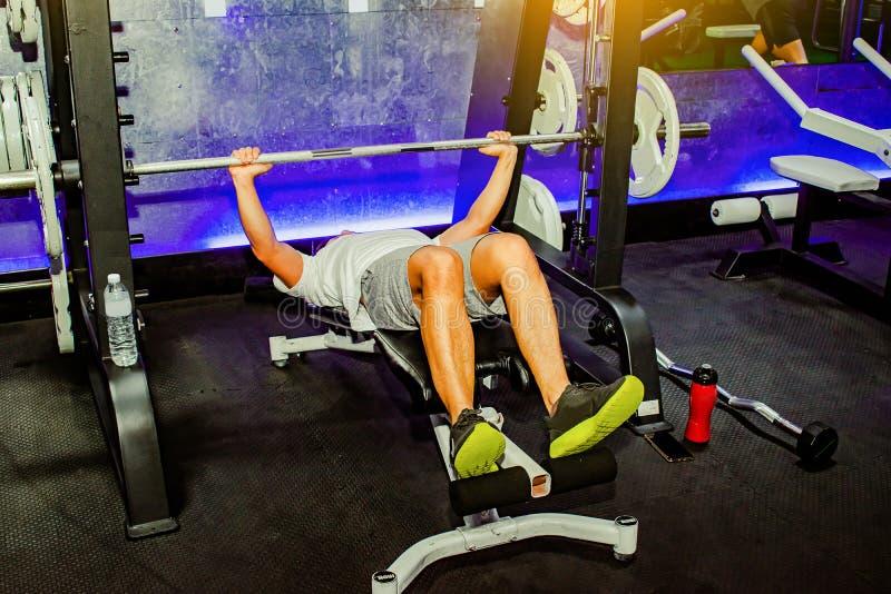 亚裔人行使在卧推人机器生活方式的胸口锻炼健身健康的 隐喻健身和锻炼概念 免版税库存照片