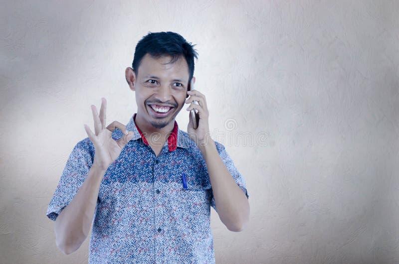 亚裔人谈话在做与手指的被隔绝的灰色背景的电话ok标志,微笑的正面做好标志用手 免版税库存照片