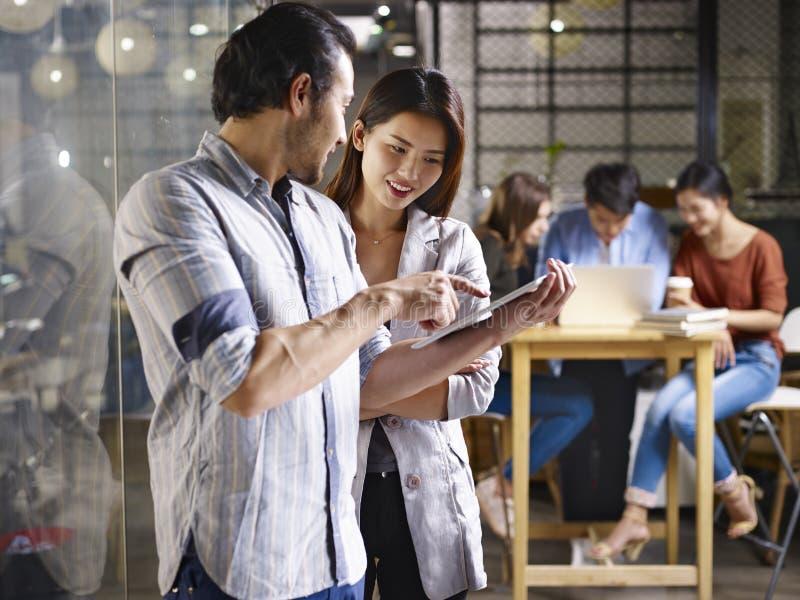 亚裔企业家谈论事务在办公室 库存照片
