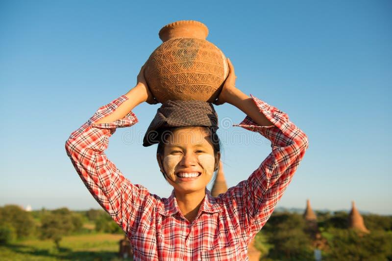 亚裔传统女性农夫运载的泥罐 免版税库存照片