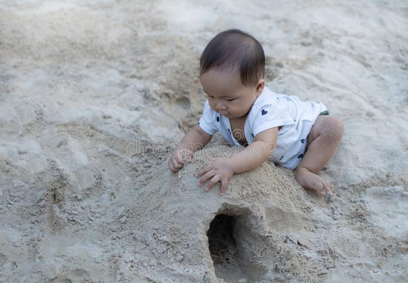亚裔使用与沙子的小孩婴孩泰国女孩 库存图片