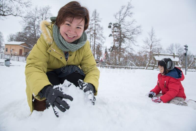 亚裔使用与雪,瑞士,欧洲的母亲和女儿 免版税库存图片