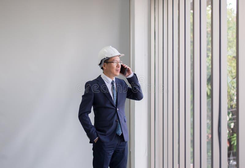 亚裔使用手机的人在现代办公楼的土木工程师和身分 图库摄影