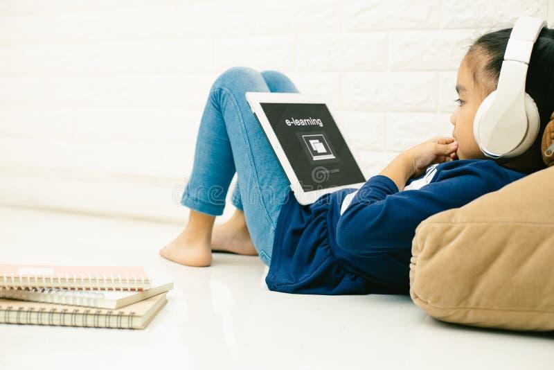 亚裔使用有题字的儿童亚裔孩子膝上型计算机在屏幕电子教学 网上教育,电子教学 免版税库存图片