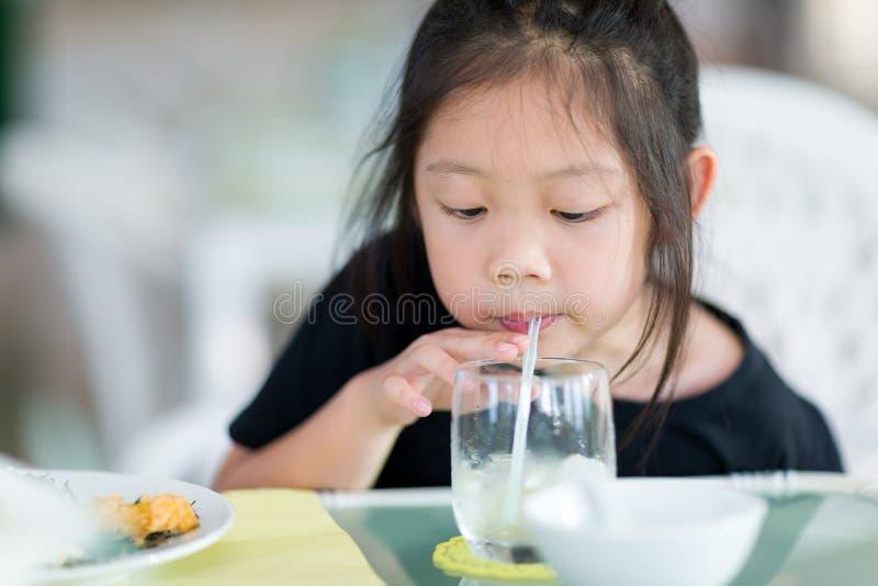 亚裔使用秸杆的儿童饮用水从玻璃 库存图片