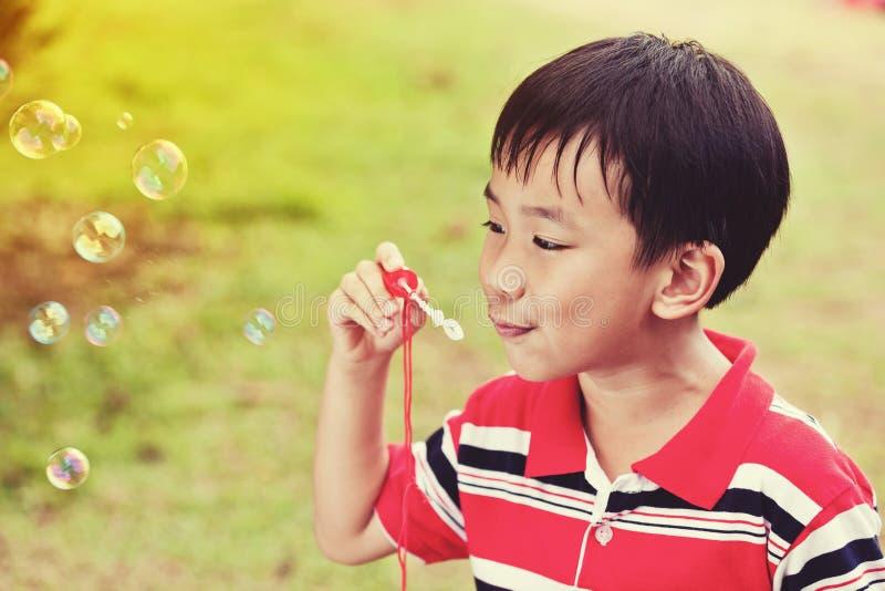 亚裔儿童吹的肥皂泡在夏天公园,自然backgrou 库存照片