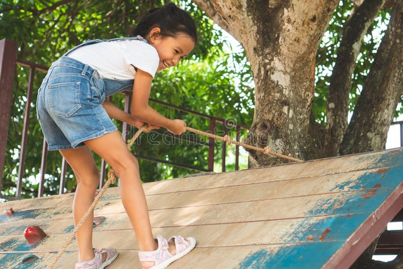 亚裔儿童女孩在有乐趣的操场攀登有一条绳索的木墙壁和强 免版税库存图片