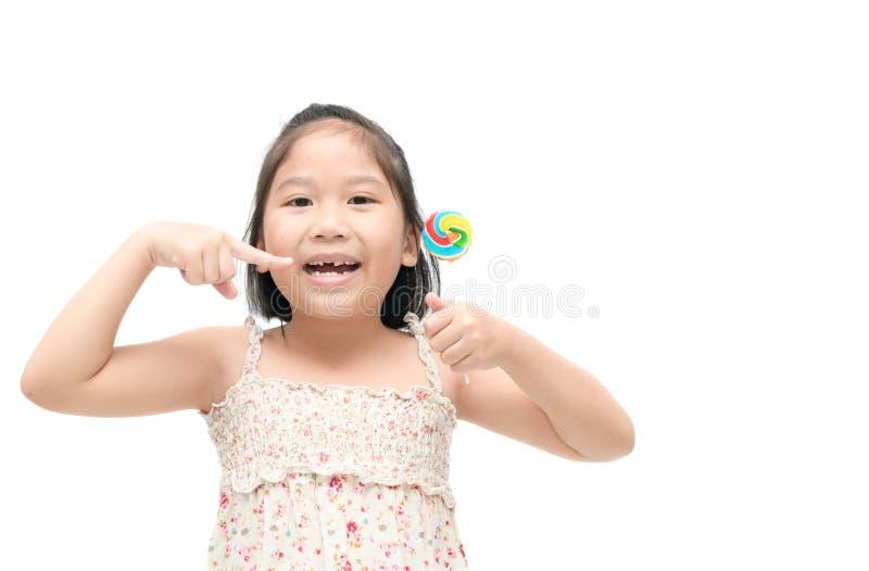 亚裔儿童女孩显示她的牙和糖果 库存照片