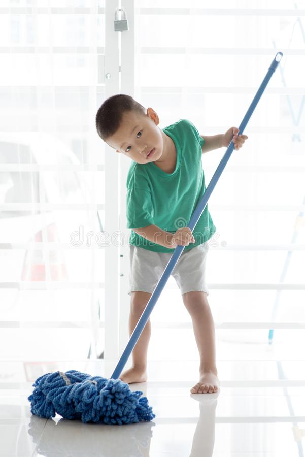 亚裔儿童擦的地板 库存图片