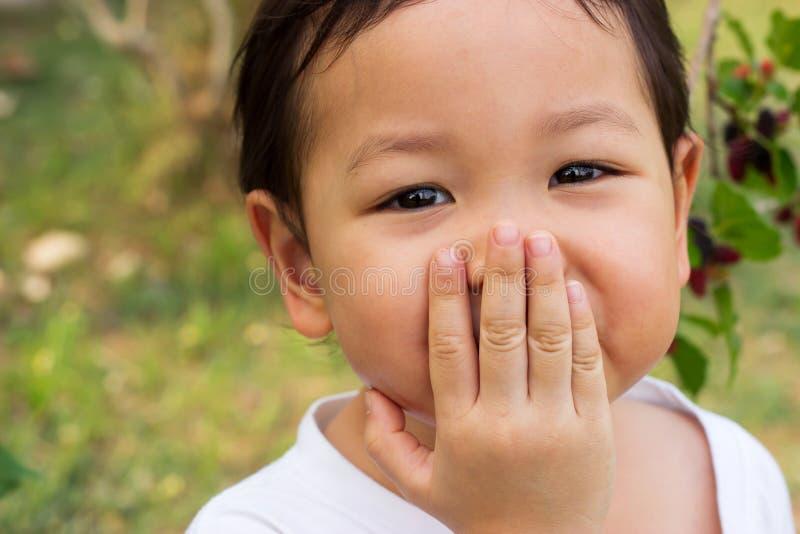 亚裔儿童笑的堵嘴 关闭在她的眼睛 感觉的幸福 免版税图库摄影