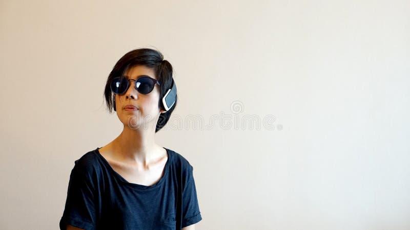 亚裔凉快的行家女孩佩带的太阳镜和耳机,城市l 库存照片