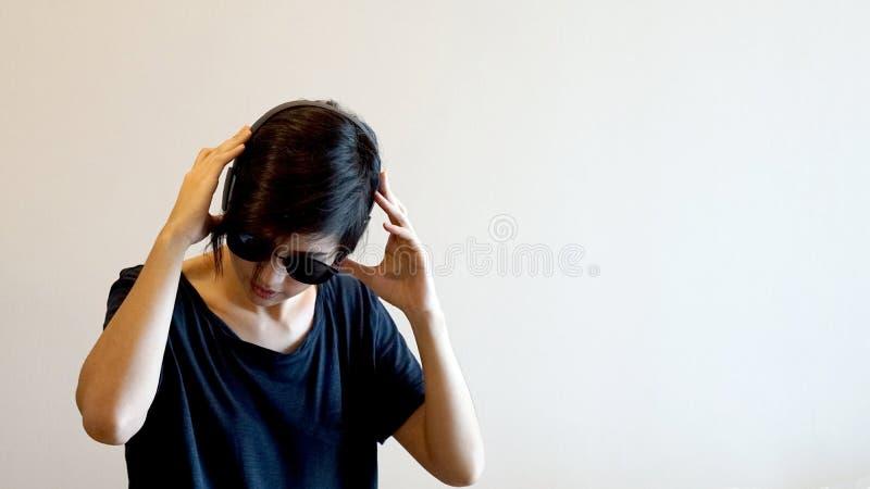 亚裔凉快的行家女孩佩带的太阳镜和耳机,城市l 库存图片