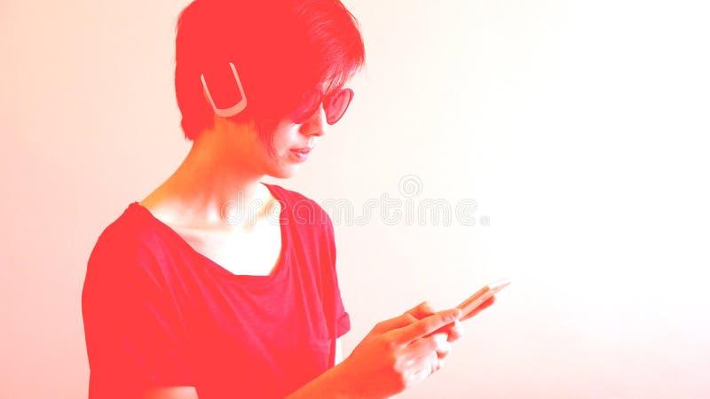 亚裔凉快的行家女孩佩带的太阳镜和耳机,都市 免版税库存照片