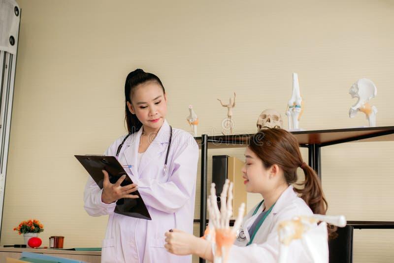 亚裔医科学生妇女教育和一起使用最基本的手大模型在医院 免版税库存图片