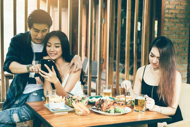 亚裔单身妇女羡慕与做作为selfie的爱夫妇在餐馆 库存图片