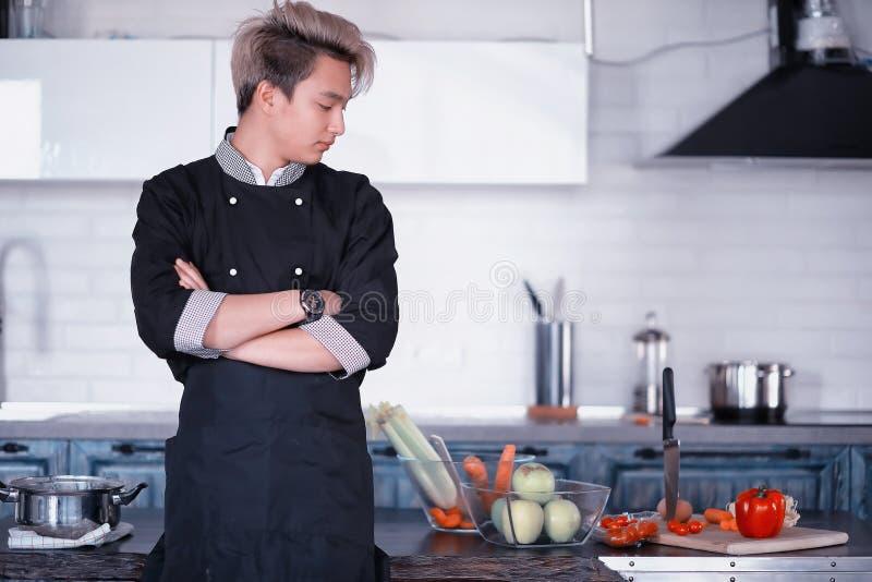 亚裔厨师在厨房准备在厨师衣服的食物 库存照片