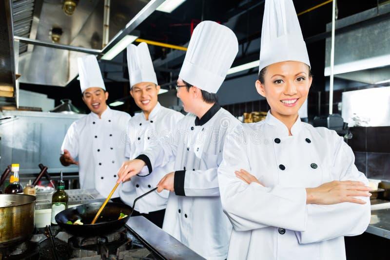 亚裔厨师在旅馆餐馆厨房里 免版税库存图片