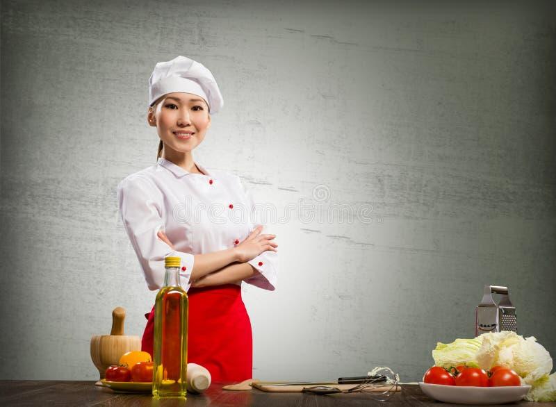 亚裔厨师妇女克服她的胳膊 免版税图库摄影