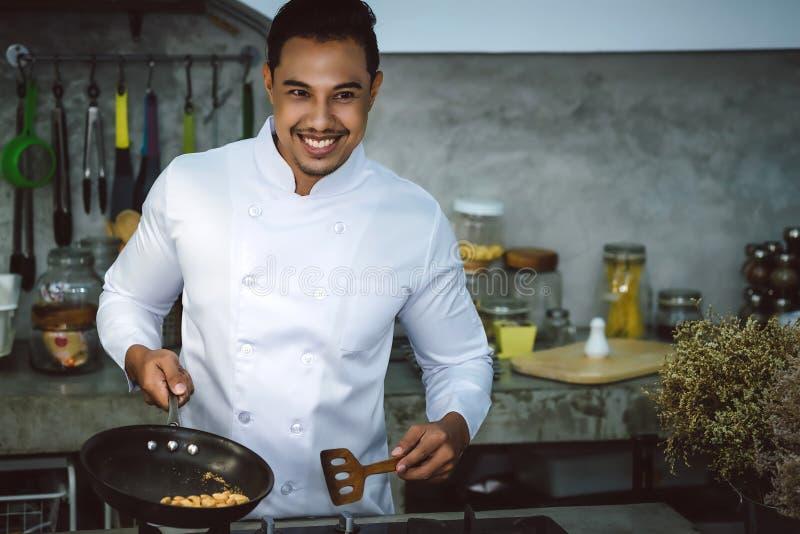 亚裔厨师,烹调是可口和熟练的 库存照片
