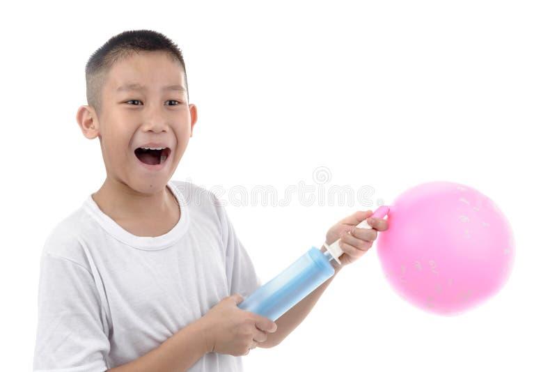 亚裔变粉红色在白色背景的气球的男孩抽的空气 免版税图库摄影