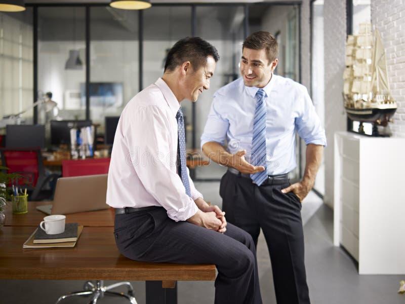 亚裔和白种人同事谈话在办公室 免版税图库摄影
