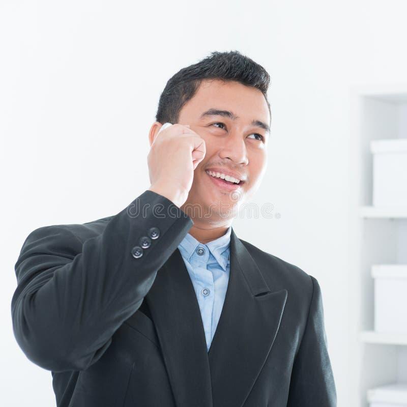 亚裔商业主管谈话在智能手机 免版税库存图片