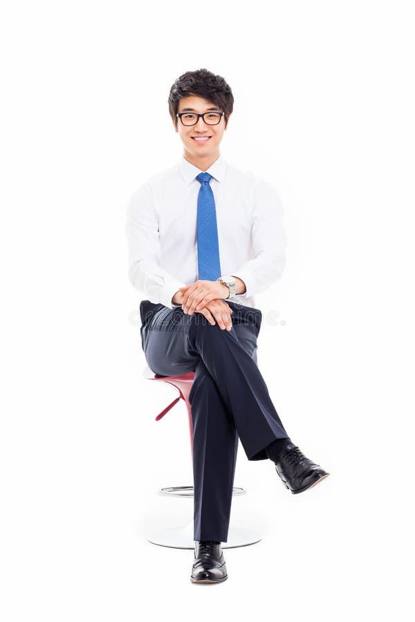 年轻亚裔商人坐椅子。 库存照片
