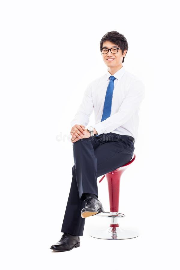 年轻亚裔商人坐椅子。 免版税图库摄影