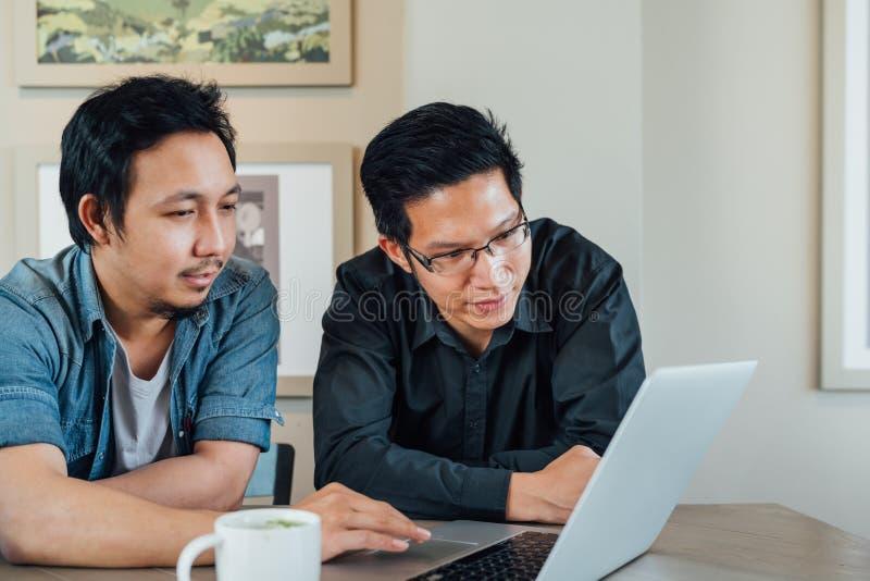 亚裔商人或商务伙伴一起谈论项目使用便携式计算机在咖啡店 队会议或配合 库存图片
