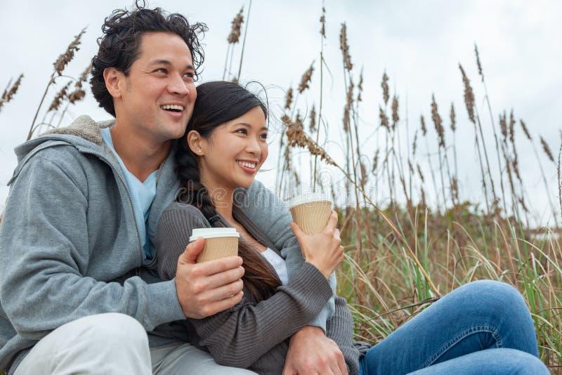 亚裔喝在海滩的人妇女浪漫夫妇外卖咖啡 免版税库存照片