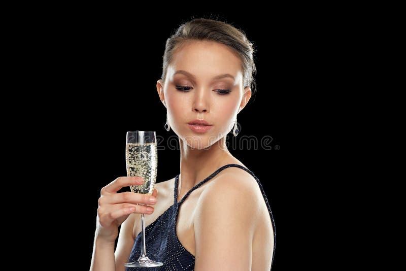 年轻亚裔在党的妇女饮用的香槟 库存照片