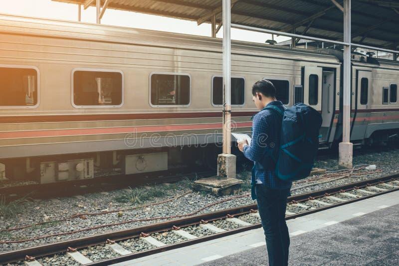 亚裔在平台和举行片剂的人等待的火车背面图  免版税库存照片