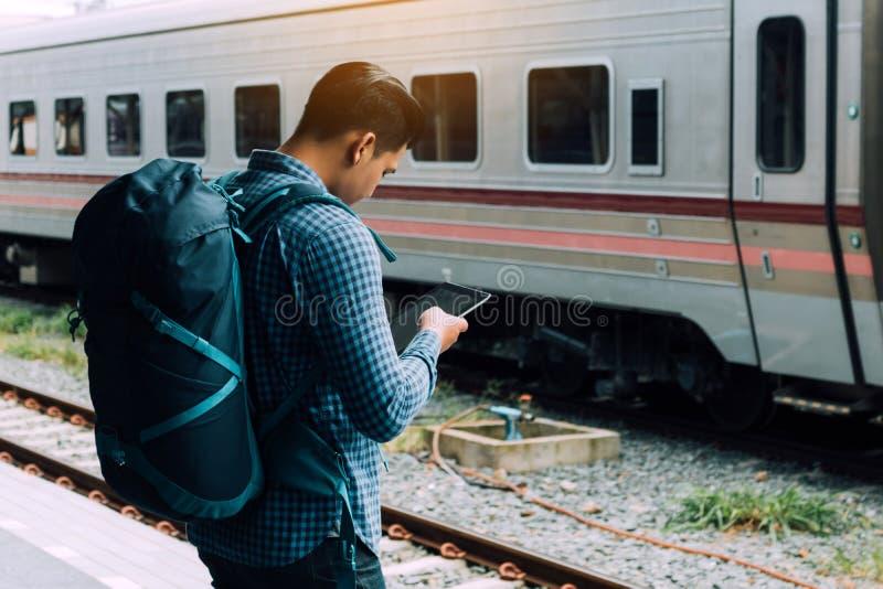 亚裔在平台和举行片剂的人等待的火车背面图  免版税库存图片