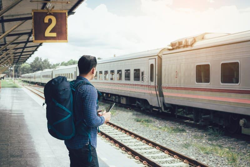 亚裔在平台和举行选项的人等待的火车背面图  库存照片
