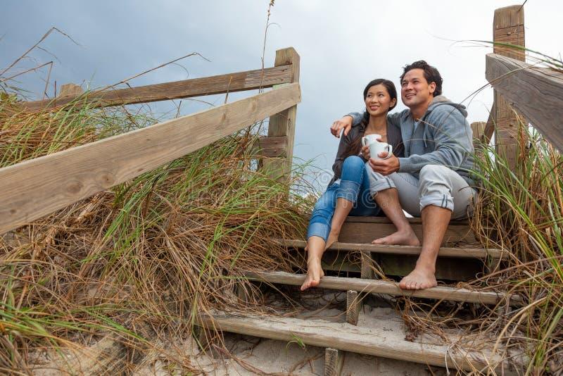 亚裔在海滩步的人妇女浪漫夫妇 免版税库存图片