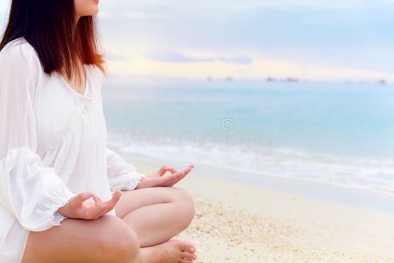 亚裔在海滩的年轻女人实践的瑜伽 图库摄影