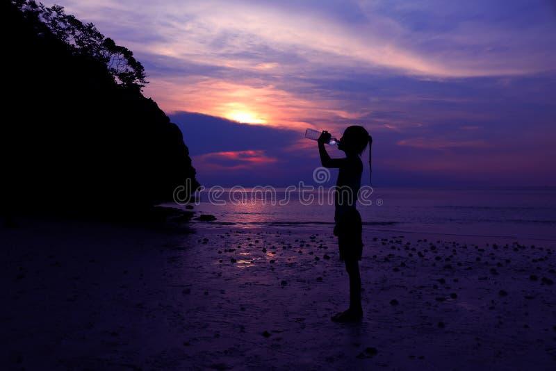 亚裔在海滩的女孩饮用水 免版税库存照片