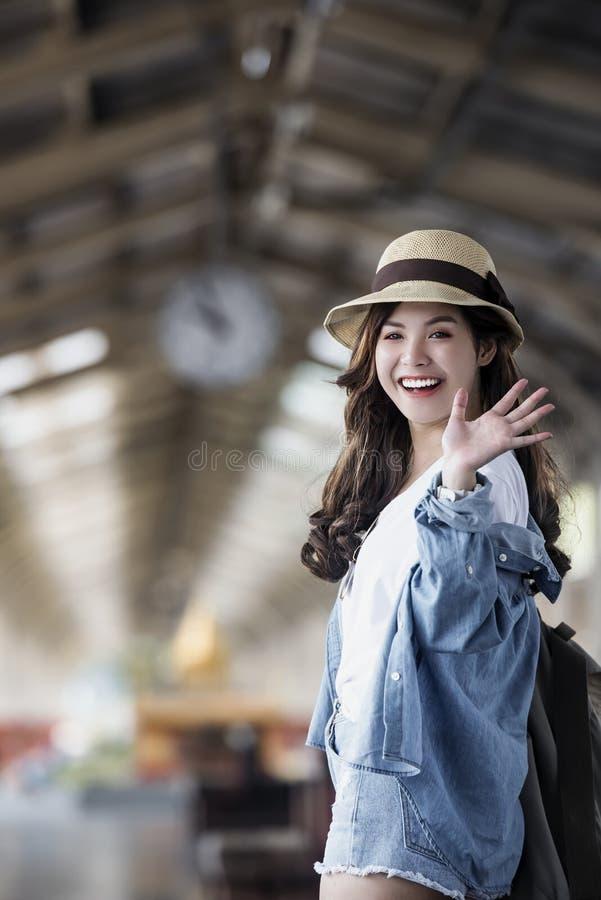 亚裔在火车站平台的背包旅客妇女微笑的和挥动的手 图库摄影