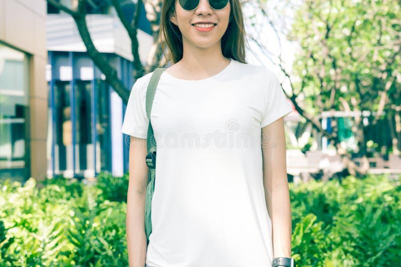 亚裔在白色空白的T恤杉的行家女孩长的棕色头发在街道中间站立 图库摄影
