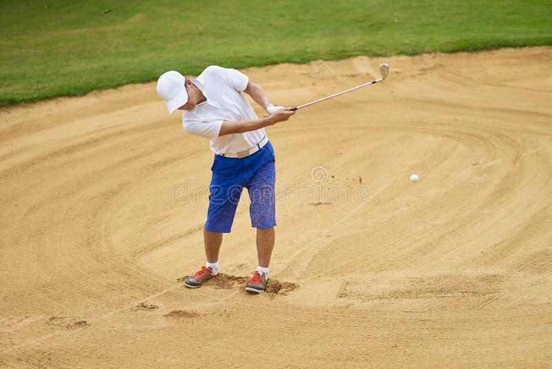 亚裔在高尔夫球场砂槽的人摇摆的高尔夫俱乐部  库存图片